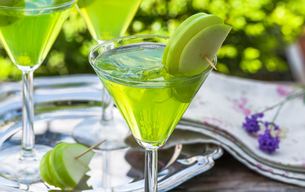 green tequila and sour apple cocktail in a martini glass