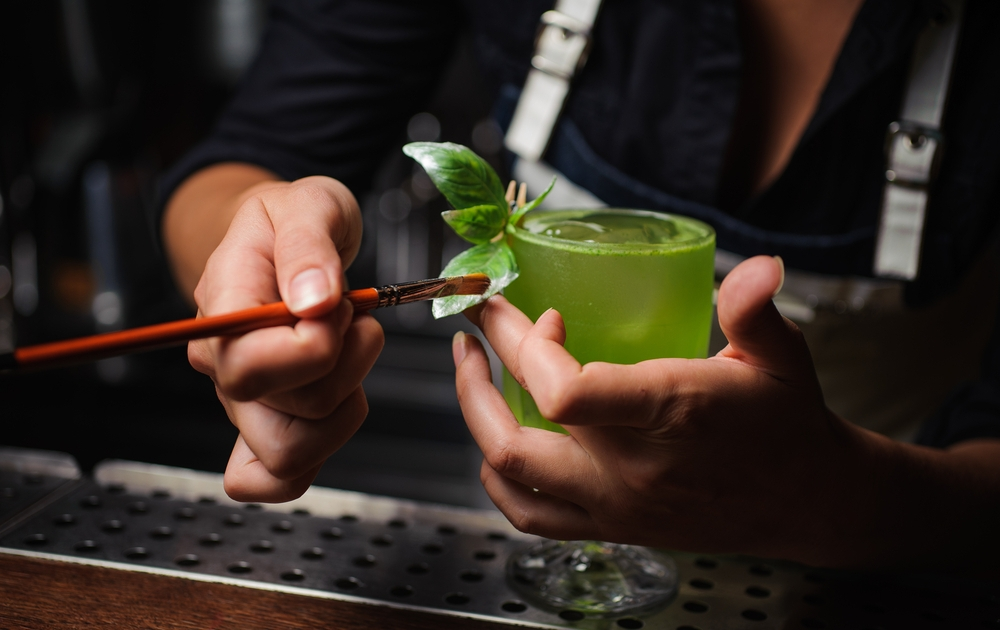 Professional Mixologist dusting cocktail drink with green food color