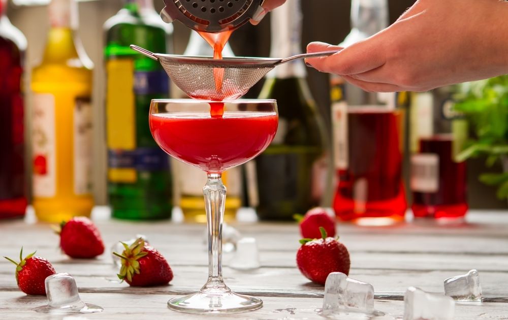 red cocktail poured by professional mixologist - fresh summer drink