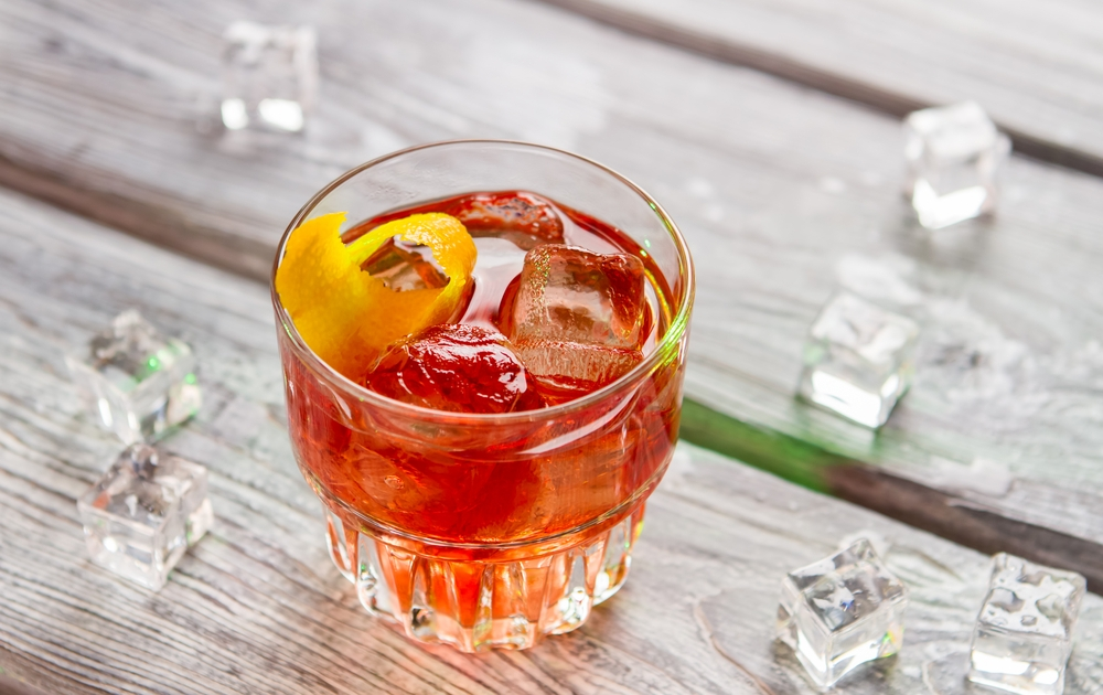 Hire A Mixologist - orange cocktail with lemon rind and ice. negroni with bitter and vermouth